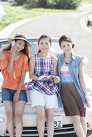 車にもたれる女性3人