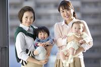 赤ちゃんを抱くビジネスウーマン2人 07900006361| 写真素材・ストックフォト・画像・イラスト素材|アマナイメージズ