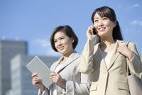タブレットPCとスマートフォンを持つビジネスウーマン2人