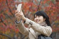 スマートフォンで撮影する女性
