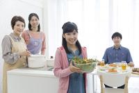 サラダを運ぶ女の子と家族