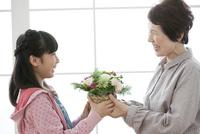 花束を渡す孫と祖母