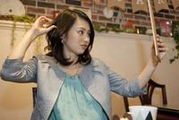 髪を整える女性 07900006881| 写真素材・ストックフォト・画像・イラスト素材|アマナイメージズ