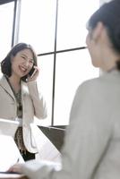 スマートフォンで話すビジネス女性