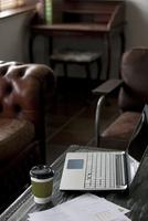 テーブルに置かれたノートパソコンとコーヒーカップと資料