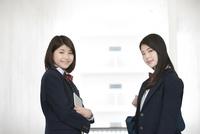 向き合う笑顔の女子高生2人 07900007327| 写真素材・ストックフォト・画像・イラスト素材|アマナイメージズ