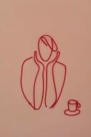 ワイヤーで作られた頬杖をつく人とカップ