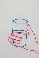 ワイヤーで作られた水の入ったコップを持つ手