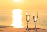 モルディブのサンセットバーで夕日を浴びるシャンパングラス