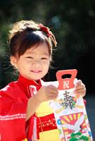 千歳飴を手に笑顔を見せる七五三の3歳の少女
