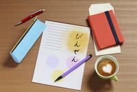机の上の便箋と筆ペンとハートマークのコーヒー