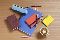 机の上のノートと万年筆とハートマークのコーヒー