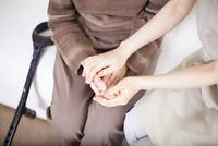 おばあちゃんと手を重ね合わせる介護士さん