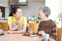 お弁当を食べるおばあちゃんと付きそう介護士の女性