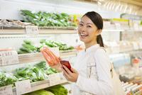 スマホを見て買い物する女性