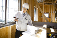 タブレットで建築中の家の中をチェックする現場監督