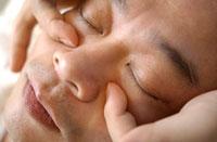 指圧で顔をマッサージされる日本人男性