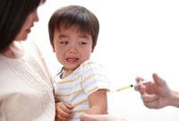 注射を打たれる子どもを抱く母親と医者