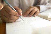 ノートに書く男子高校生の手