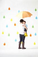 カラフルな雨のしずくバックでオレンジの傘を差す親子