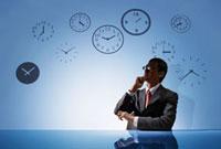 時計の背景の前で考えごとをするビジネスマン 10132105811| 写真素材・ストックフォト・画像・イラスト素材|アマナイメージズ