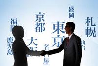 様々な地名の文字の前で握手し合う男性2人