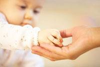 積み木のおもちゃを渡す赤ちゃんの手とお母さんの手