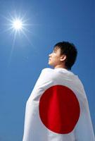 日本の国旗を背中に背負う男性