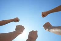 青空に力強くこぶしを突き上げる3人の男性の手
