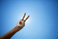 日本の国旗が描かれた手でピースをする手