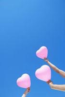 青空にピンクのハートの風船を持つ三人の手