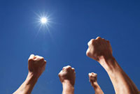 太陽に向かって強く突き上げられた4本の腕