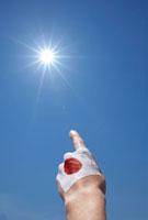 太陽に向かって指差す日本国旗をペイントした手