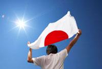 日本の国旗をなびかせる男性の後ろ姿