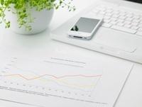 パソコンとグラフ資料とスマートフォンが乗ったビジネスデスク