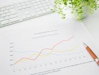 グラフ資料とペンと観葉植物とキーボードが乗ったビジネスデスク