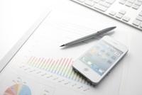 キーボードとスマートフォンとグラフ資料が乗ったビジネスデスク