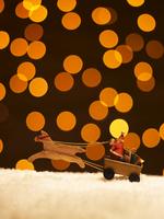 イルミネーション背景の雪の上を走るトナカイとサンタの人形