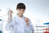試験管にスポイトで薬品を入れている女性研究員
