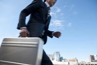 アタッシュケースを持って走っているビジネススーツを着た男性 10132107253| 写真素材・ストックフォト・画像・イラスト素材|アマナイメージズ