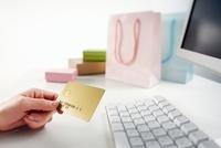 パソコンの前でクレジットカードを持っている女性の手