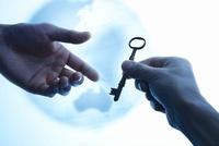 地球儀を背景にアンティークな鍵を渡そうとしている2本の手