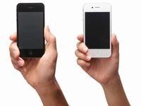 黒いスマートフォンを持つ手と白いスマートフォンを持つ手