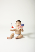 座って日本とアメリカの国旗をふる裸の赤ちゃん
