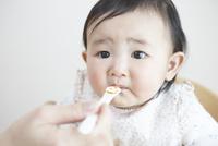 お母さんにスプーンで離乳食を食べさせてもらう女の子の赤ちゃん