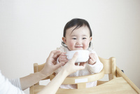 お母さんにスープを食べさせてもらう赤ちゃん