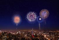 都市の夜景に浮かぶ花火の背景素材
