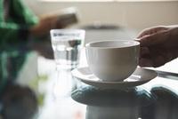 ラウンジでテーブルの上のコーヒーを飲む