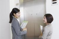 エレベーター前で会話するスーツの女性