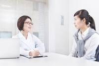 社内にてカウンセリングをする女性社員とカウンセラー